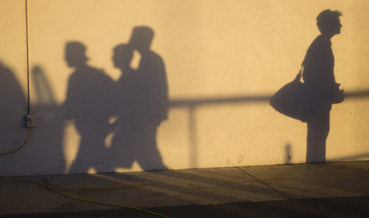 The silhouettes reveal 3 unknown Cam High students as they walk by a car, an elder woman patiently waiting behind them.
