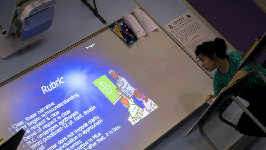 Natalie McIntyre, senior at Mr. Mark Storer's English 4 class, takes notes that are projected from the smartboard.