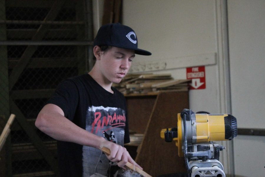 A student cleans off his work space after working on his Wood Shop project.