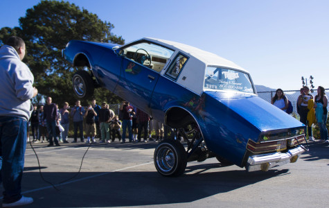 Students gather around to watch a hydraulic system launch this car up into the air.