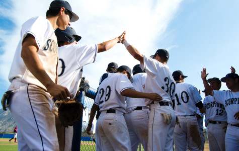 The Baseball team high-fives each other after a successful run at a Varsity game.