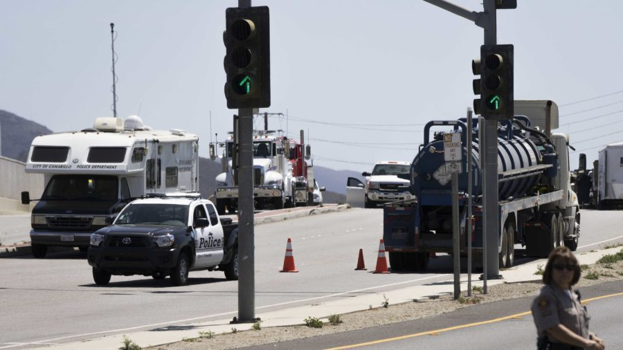 Camarillo police officers make sure that the cleanup crew is able to work without any disturbance at the site of the oil-tanker crash this morning near Cam High.