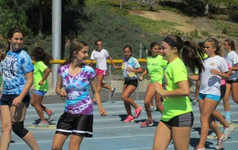 Girls from Cam High's track team perform warm-ups Thursday. Cam High's track team will begin competing in the Coastal Canyon league from now on.