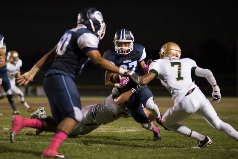 Cam High football player tries to make it past Saint Bonnie's defensive line.