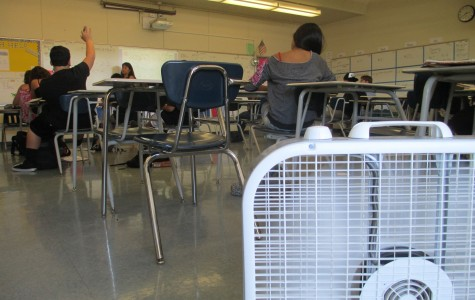 Mrs. Katie Frederick teaches as her two fans guard the classroom's entrance in an attempt to combat rising temperatures.