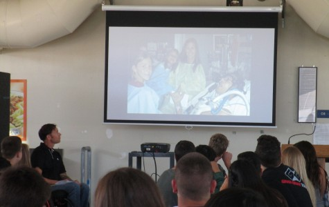 Guest speaker Tony Pedeferri (bottom left) shows his audience a video composed of pictures before and after his tragic accident, as well as broadcasted footage after the crash. Shown here is a picture of his recovery in the hospital with his wife and two daughters at his side.