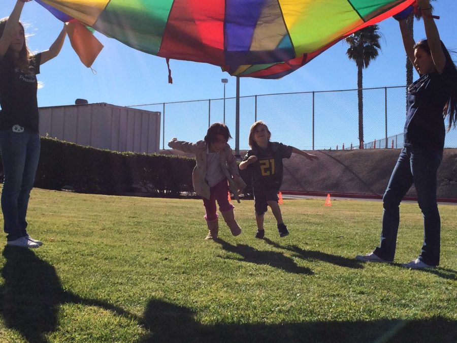 Two members of the Little Scorps Program play the parachute game during class on the quad. Little Scorps is a pre-school program run by Cam High students and Mrs. Ida Lange, instructor.
