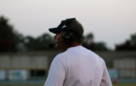 Coach Jack Willard watching the varsity football team during a Friday night game.