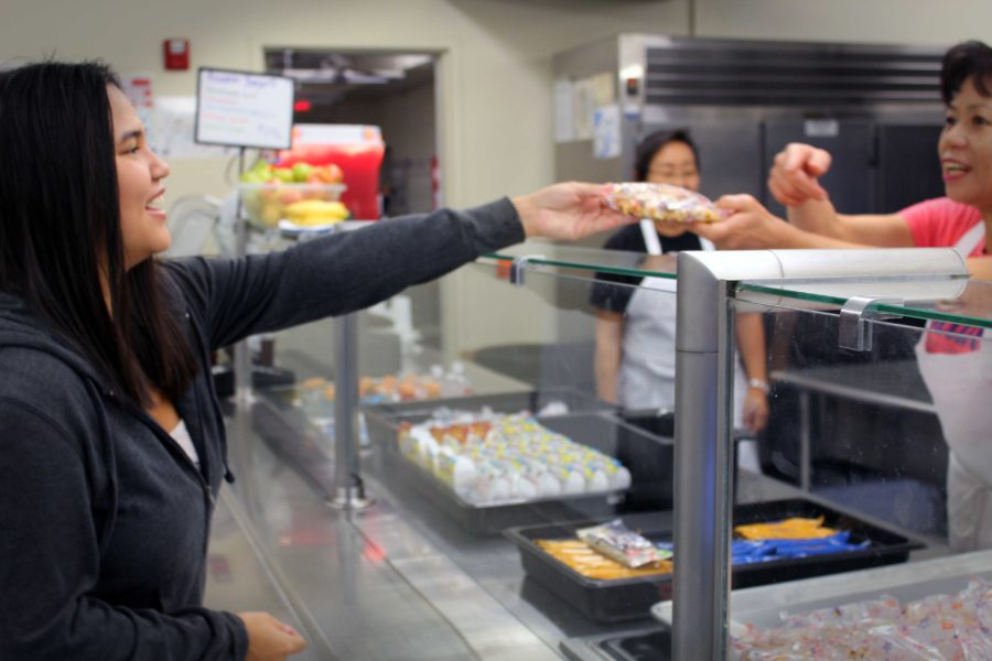 Kiyoko Aoki, senior, purchases breakfast in the cafeteria before school.