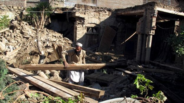 A man clears debris of a fallen house after the Pakistan earthquake.