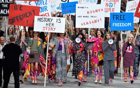 Chanel models walk the catwalk in a finale featuring empowering signs and megaphones.
