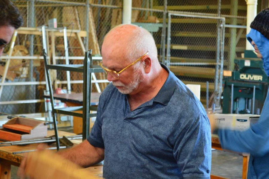 Mr Mills, who will retire at the end of the school year, helps a student with a project in his sixth period wood shop class.