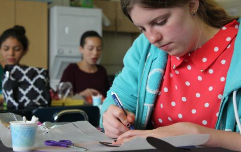 Senior Stephanie Sust constructs a mosaic tissue paper stained glass heart in Craft Club.