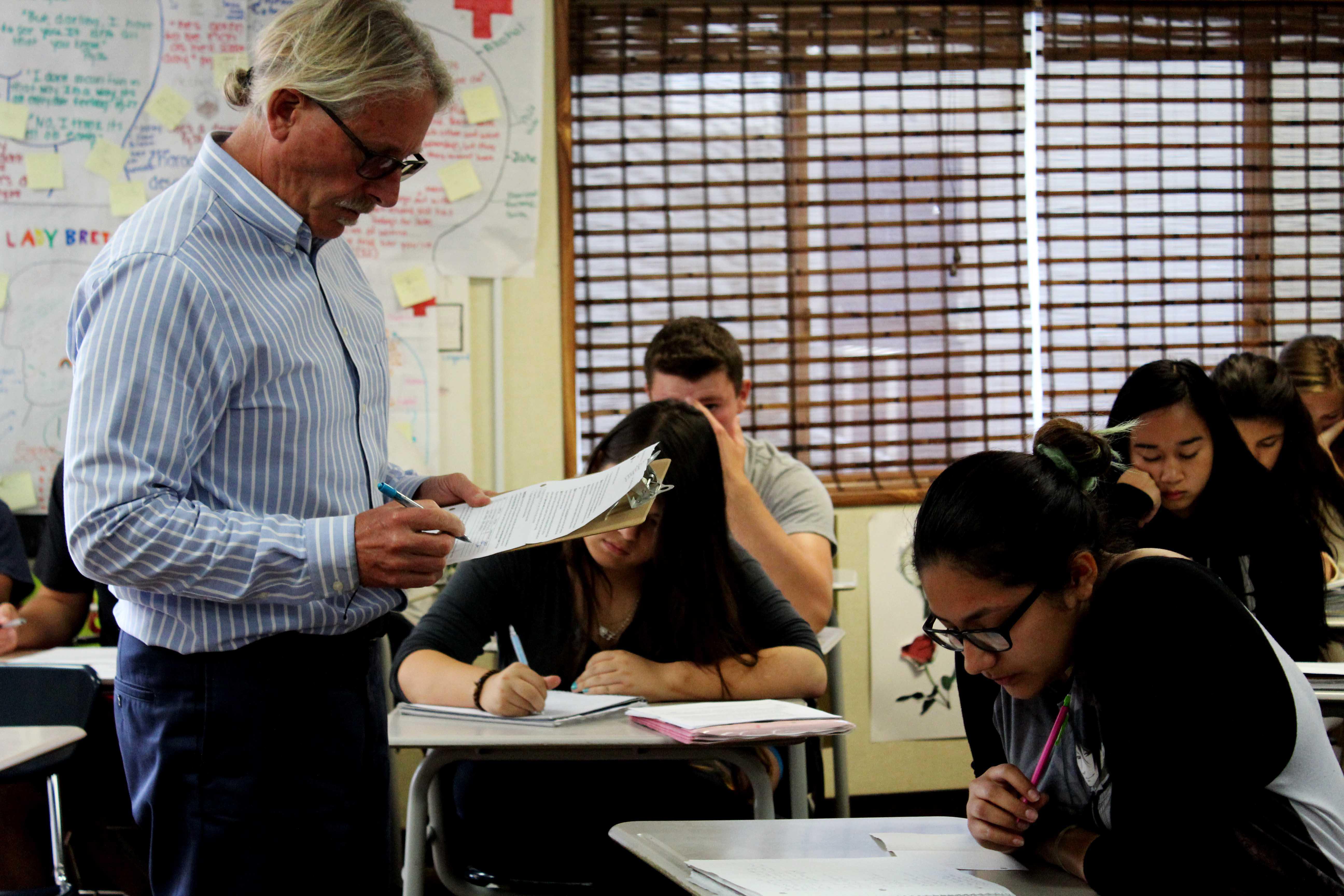 Mr. Kevin Buddhu reviews his English 3 class' homework assignments.