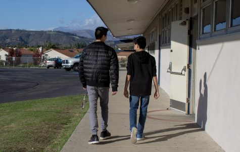 Brothers Adam Fujii, freshman, and Brandon Fujii, senior, walk pass the C-building while Brandon shares some high school advice.