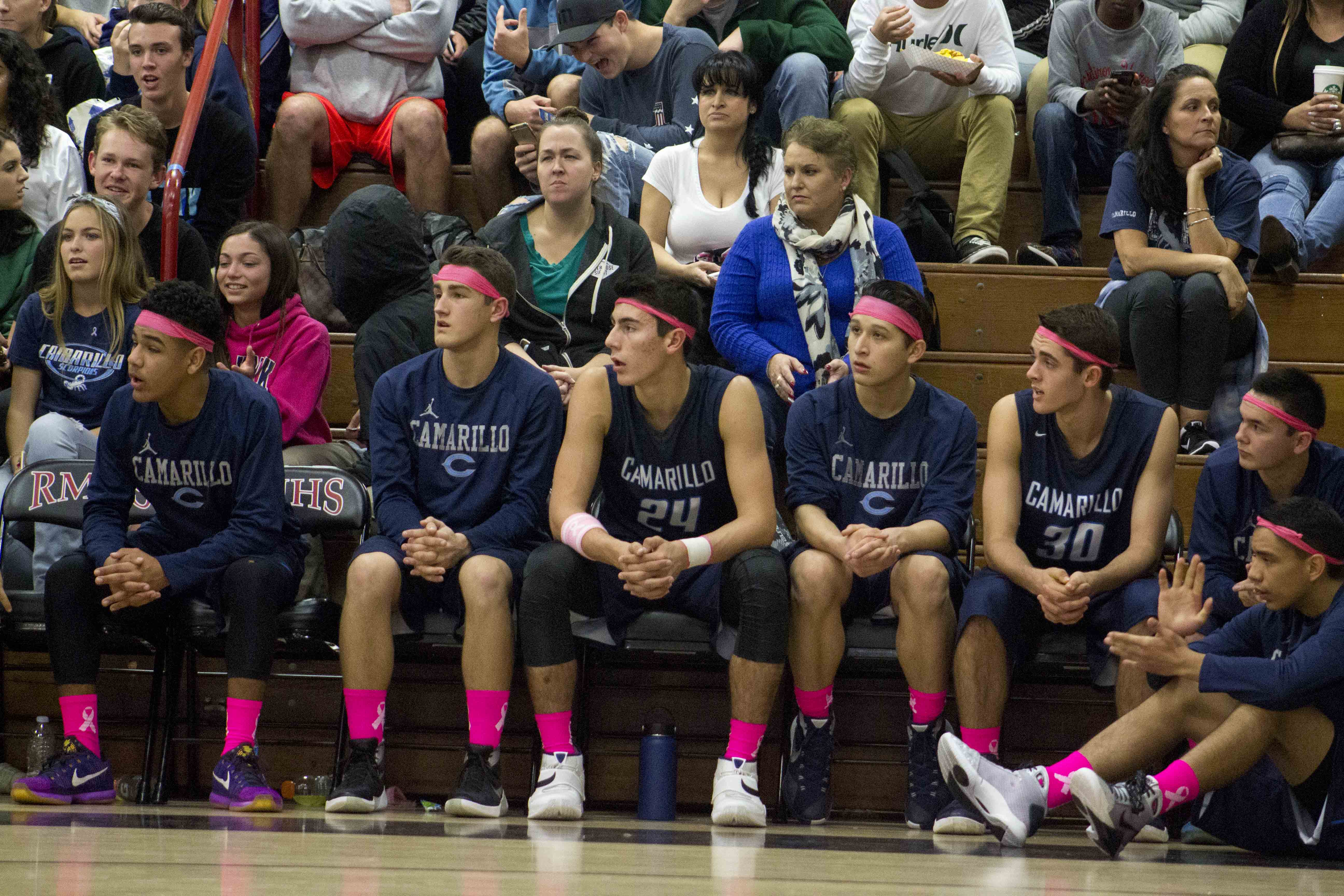 Boys varsity players watches on from the bench.