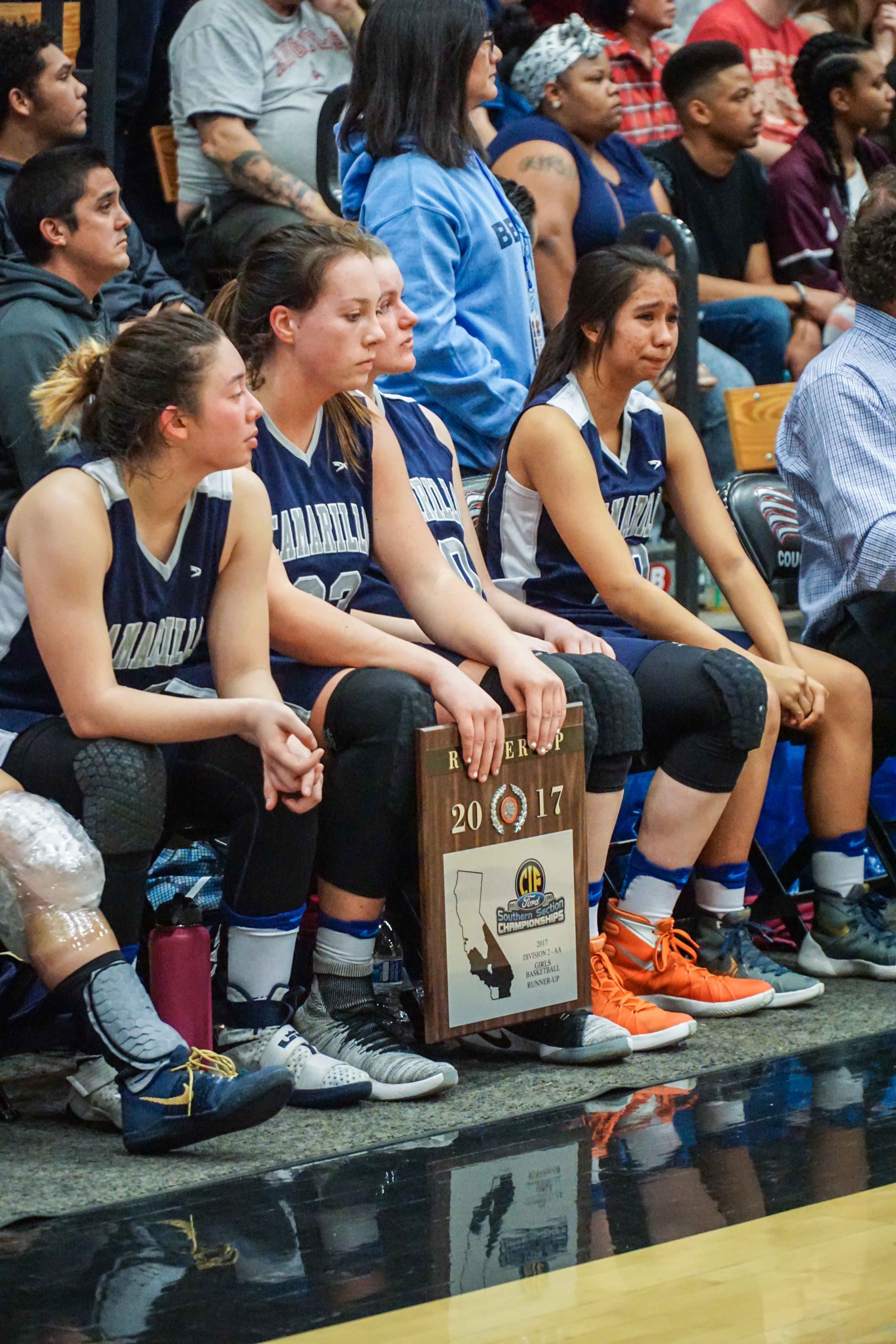 Teammates sit court-side with their runner-up plaque.