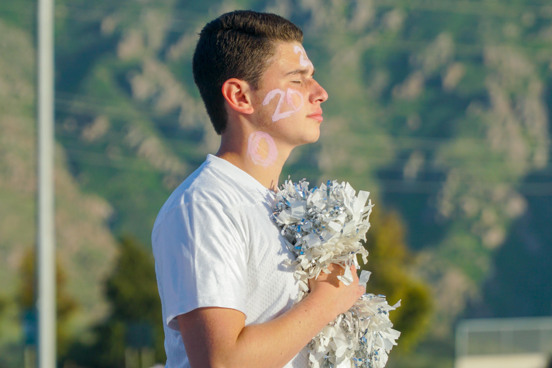 Bryce Skolnick, senior, holds his pom poms during national anthem.