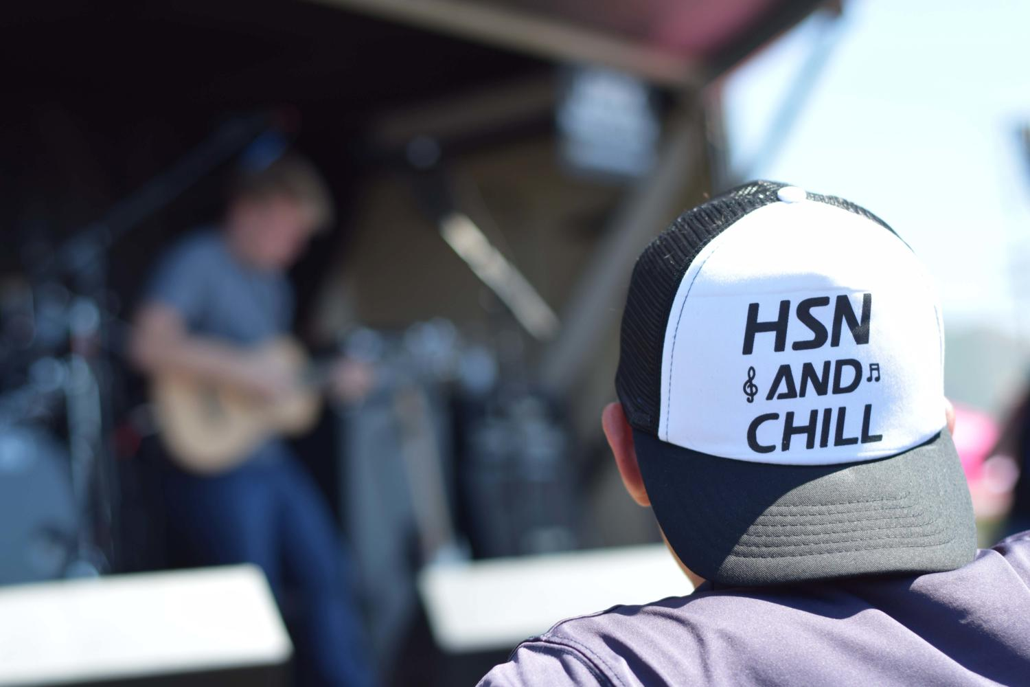 A student watches performer Jack Vandervelde on the main stage wearing High School Nation merchandise.