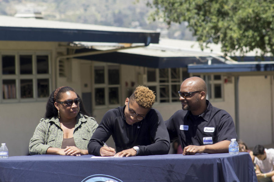 Jonah Cottrell, senior, signing for UC Merced with his parents.