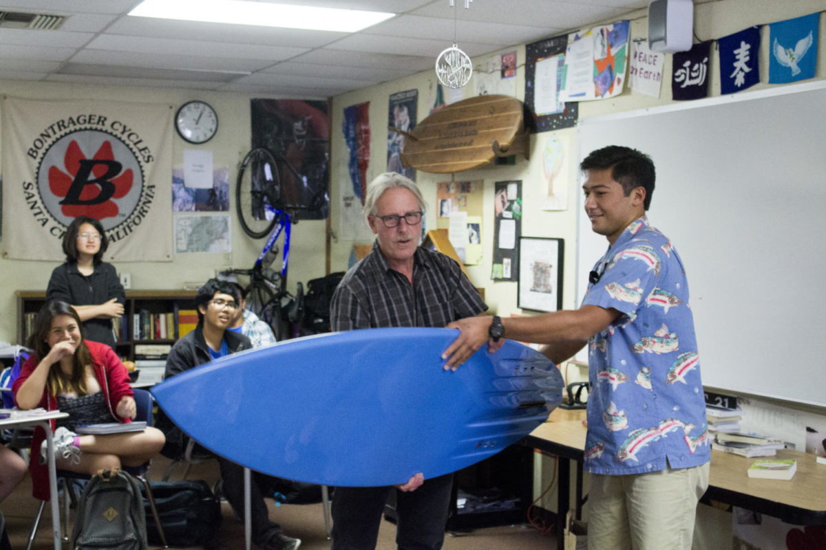 Senior+Tyler+Tsuji+hands+Mr.+Kevin+Buddhu+his+customized+surfboard+presented+by+his+AP+Literature+classes+as+a+goodbye+gift+before+he+leaves+to+Spain.