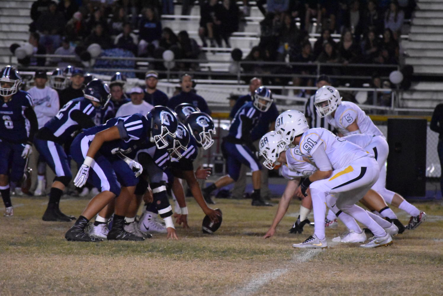Cam High's varsity football team stands head to head with Ventura High School's varsity football team before the next down.