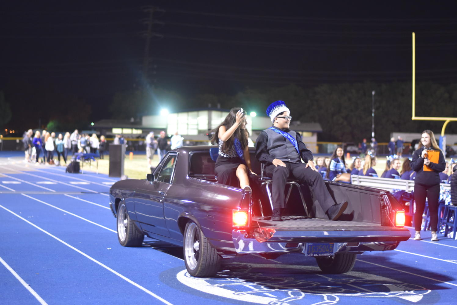 Freshman homecoming princess,Xasha Francisco, and Freshman Homecoming Prince, Fletcher Gravel, wave to their peers during halftime.