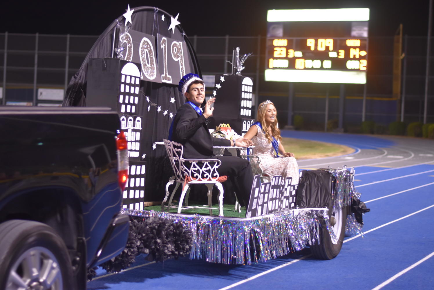 Junior Homecoming Prince and Princess, Jamie Jaquez and Ciera Muscarella, wave to the crowd as they ride in their float during halftime.