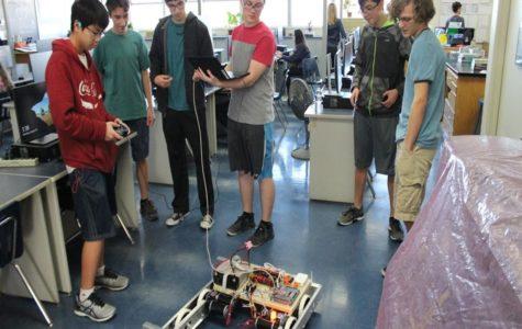 Robotics team gathers around their robot at week 2 of construction.