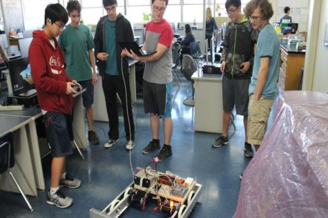 Robotics team gathers around their robot at week 2 of construction.
