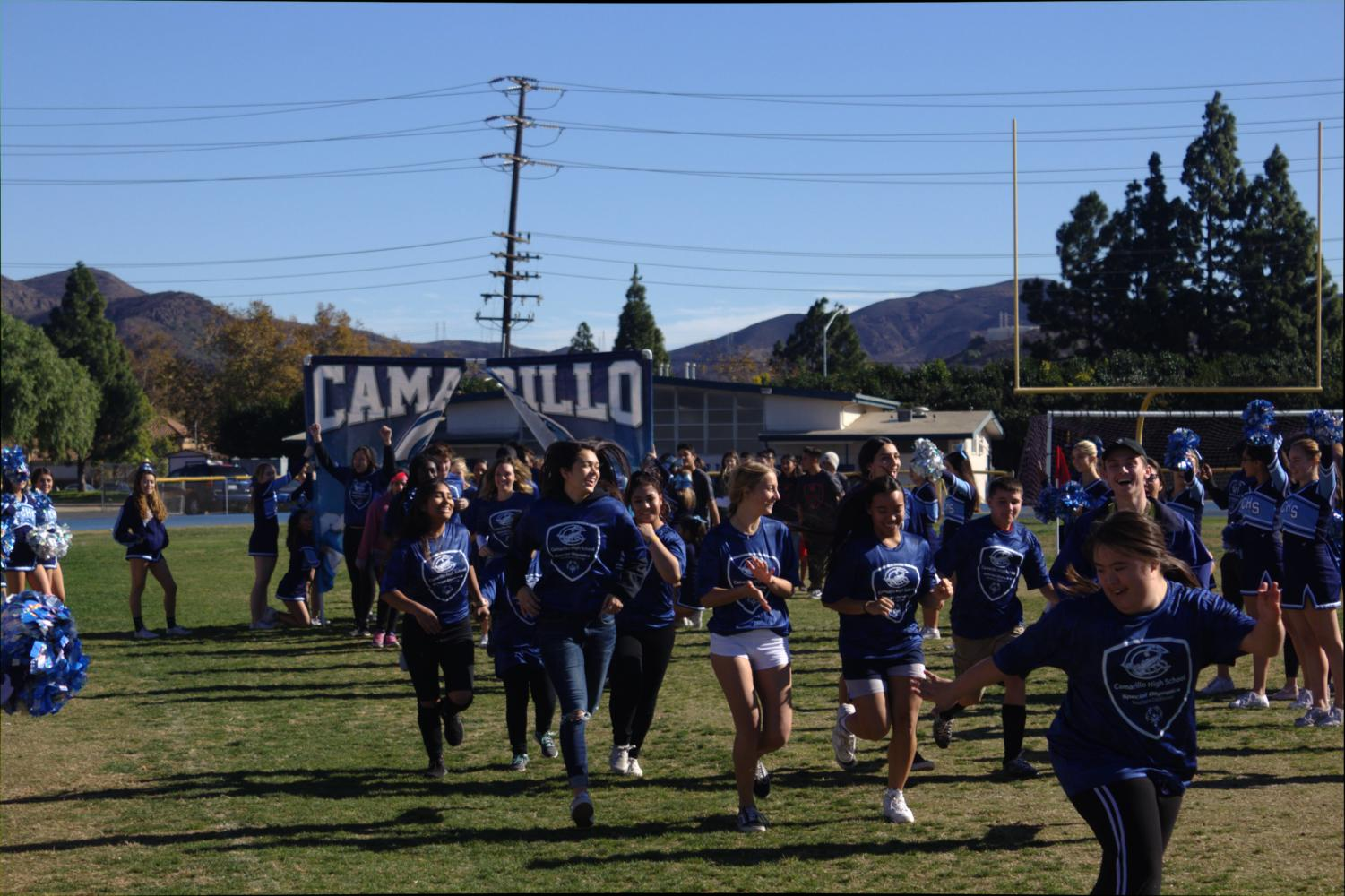 Special Ed and Regular Ed students kick off the Special Olympics soccer game by running through a Cam High banner on Dec. 4, 2018.