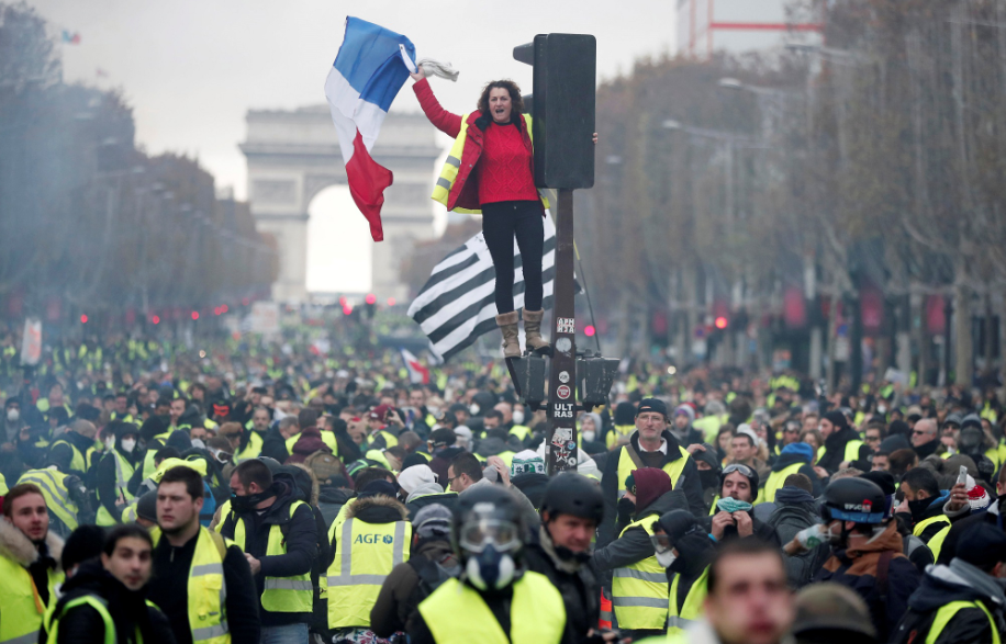 A woman waves a French flag in Paris during the protest of the French government's new fuel tax.