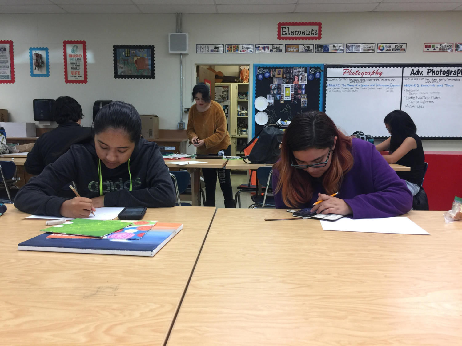 Christina Roa (left) and Lauren Ruiz (right) working on a paper mache project during the art club meeting on Dec. 12.