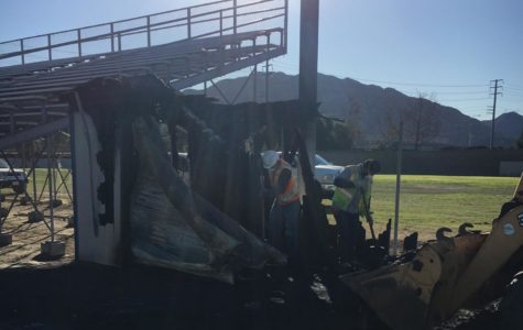 The burnt shed is located by the visitor's bleachers in Cam High's stadium.